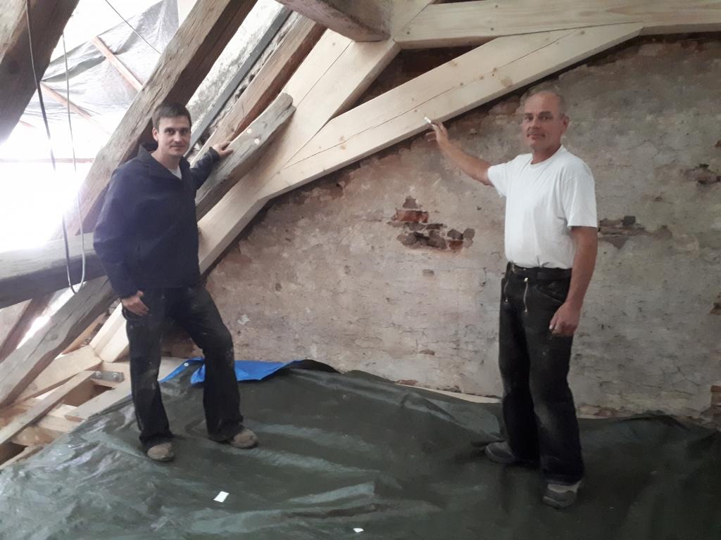 Die Zimmerleute zeigen die neu eingefügten Balken und Streben.